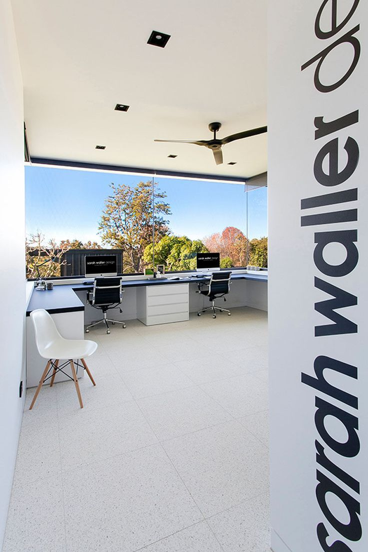 This home office of an architect looks out over the backyard from the wrap around windows.