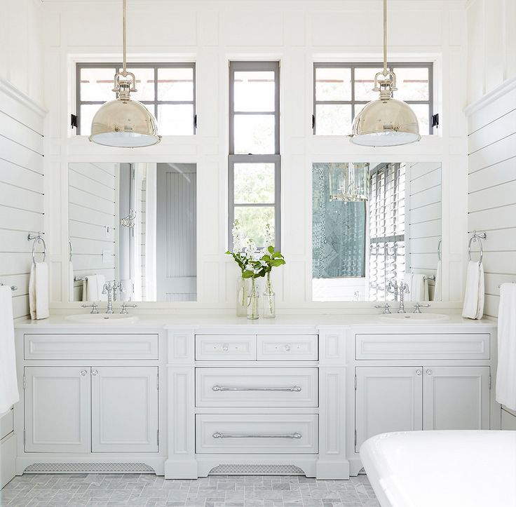 White cottage bathroom features a built-in dual vanity fitted with his and her porcelain sinks ...