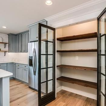 This traditional kitchen optimizes its space using a built-in pantry with glass doors and stacked salvaged wood shelving | Dream Book Designs