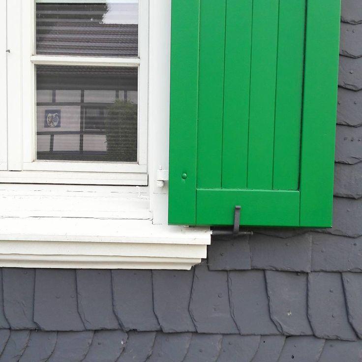 Bergisches Architektur- Detail: Fenster samt Laden in typischem Grün • In der Spiegelung zu sehen: ein Fachwerkhaus