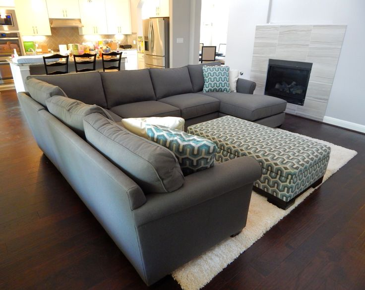 The Benjamin sectional by Jonathan Louis is probably one of the most versatile pieces of transitional furniture in our store. It has the rolled arms of traditional sofas, but the square shapes and tapered legs often found in modern designs. It looks fantastic in this modern living room with these custom-selected patterned pillows and ottoman.