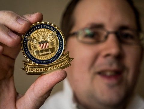 "The ""challenge coin"" no longer features the presidential seal or national motto. But it does have ""Make America Great Again"" — twice."
