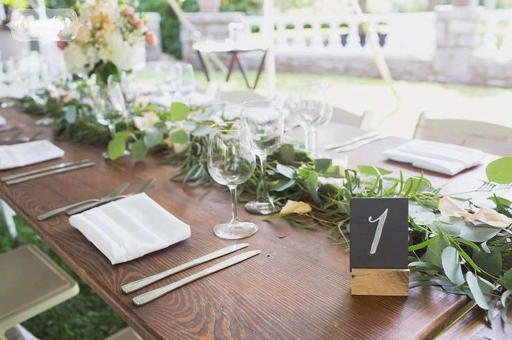 Wooden harvest tables for backyard wedding with simple wood and chalkboard table numbers in Manchester-by-the-Sea.