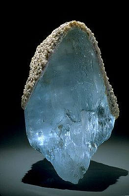 Topaz with lepidolite. Most topaz come from pegmatites. This large crystal capped with lepidolite is naturally blue. This is rare in nature, however, and most blue topaz is man-made by irradiating and heating colorless or yellow-brown topaz.