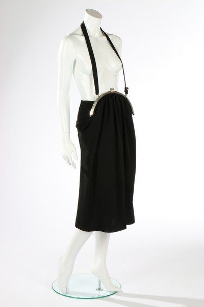 * Yohji Yamamoto purse/pinafore dress, Spring-Summer, 2001. lightweight black wool, front skirt with integral purse with metal mounts and clasp, the strap forming a halter-neck