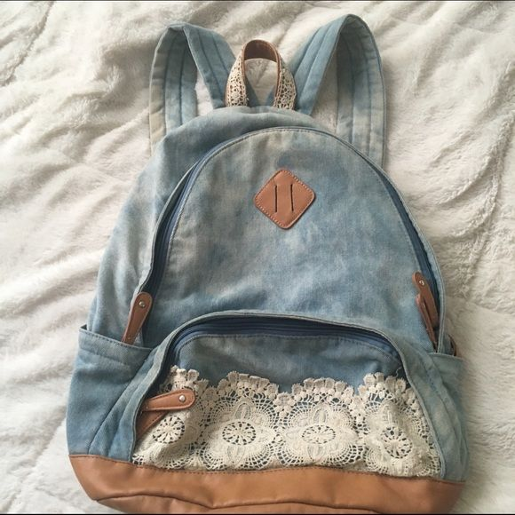 Denim and Lace Bookbag Hobo chic festival style backpack. Slight rust staining on the adjustable straps from metal adjusters. Average size Bookbag - fits text books. Divider pocket inside. Kind of an acid washed Jean print Boho Bags Backpacks