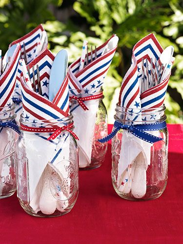 Napkins & utensils tucked in Ball jars begin a 4th of July as a table decoration & then become a practical way to give each guest a cup & silverware.