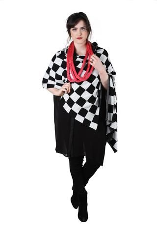 Bold black and white check patternwrap - fabulous for bringing your black outfits to life this Winter.Super soft polyester / acrylic / nylon / wool blend. Button detail down front edge so it can be worn as a wrap or undone as a scarf.
