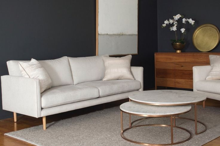 """Cream Nellie 2.5 seat sofa styled in a luxe setting with the Jarvis buffet in spotted gum, a white orchid flower arrangement, Elle marble round nested coffee tables, neutral art """"Adrift"""" and taupe wooden rug"""