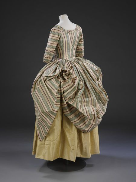 A style introduced in the 1770s called a polonaise. Using buttons and loops, the skirt of the gown was draped up to create the swathed effect at the back shown here. Also popular during this decade were a range of striped fabrics, often in a complex arrangement of colours with both sharp and shaded edges, as seen in this example. Draping the skirt was not only a fashionable option. It also served as a practical method of raising the skirt above the dirt and dust on the ground.