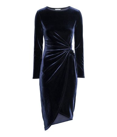 Dark blue. Long-sleeved dress in soft fabric with a knot detail at waist and asymmetric wrapover skirt.