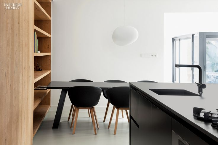 Bookshelves in the dining area can be concealed when the panel slides over from the kitchen. Photography by Ewout Huibers.