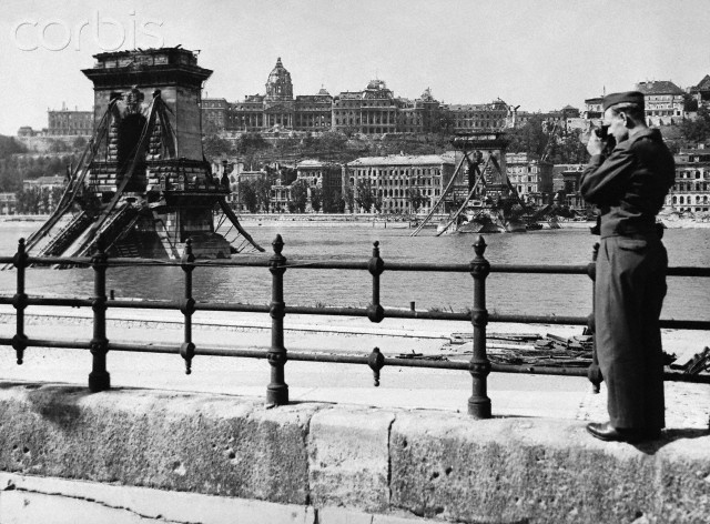 Original caption:An American soldier in Budapest takes a photograph of the famous Budapest suspension bridge, built by an English engineer, Adam Clarke, which was destroyed during the fighting for the city. In the background is seen the shell of the Royal palace, badly gutted. ca. 1945