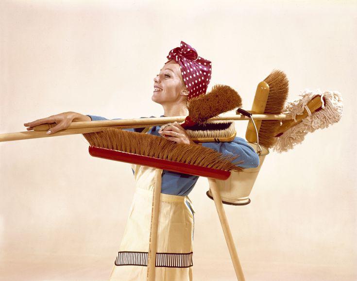 Grote schoonmaak. Huisvrouw met schort en doekje om het hoofd, gewapend met emmer, vegers en bezems, klaar voor de voorjaarsschoonmaak. Nederland, 1964.