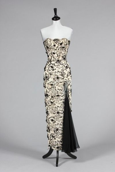A Ceil Chapman black and ivory beaded guipure evening gown, 1950s, labelled, the strapless figure-hugging sheath with silkcord wrapped flowerheads, beaded pendants and chiffon kick pleat to skirt, bust 81-86cm, 32-34in, waist 56cm, 22in Provenance: Anne Dettmer collection. This gown was acquired from the Ceil Chapman estate and was made by Ceil for her daughter- in-law. photo print ad museum