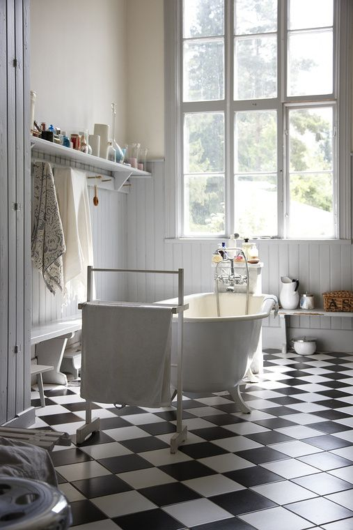 Oh to have a roll top bath sitting on black and white tiles (with underfloor heating)
