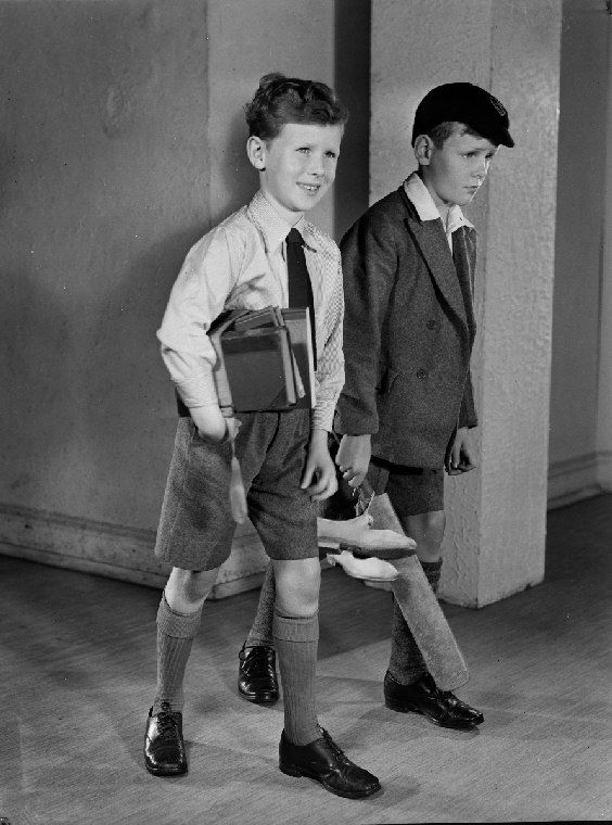 Photographic Advertising Limited  Date:    c. 1950  Description:    A photograph of two boys wearing school uniform, taken by Photographic Advertising Limited, c. 1950.    Two boys walk along a corridor, one carrying a cricket bat and the other, books. Photographs of bright, smiling boys and girls were used by advertisers to promote a wide range of products - this one is more specific in showing school life.