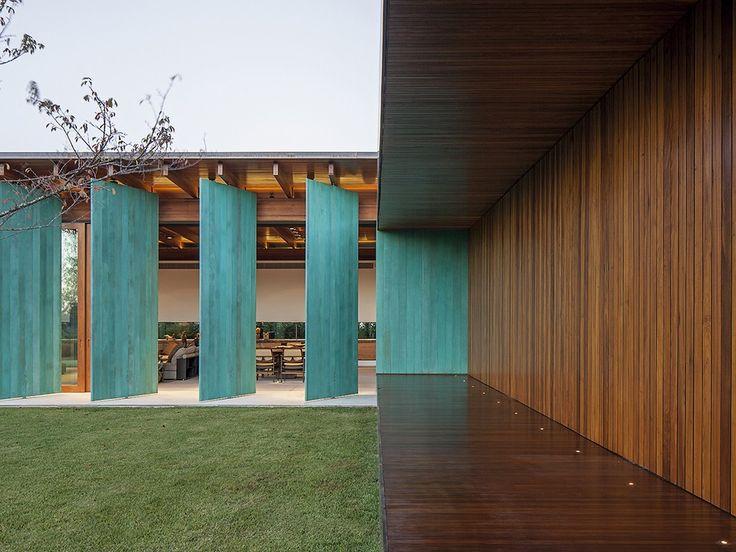 portas giratórias verdes em fachada de casa
