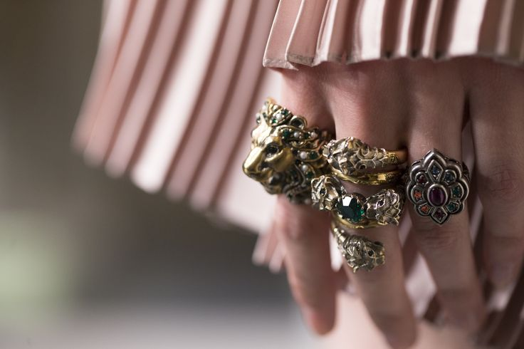 Gucci's New Ring Collection: Fistfuls of rings featuring lion and tiger head designs in golds and silvers adorned with colorful crystals.