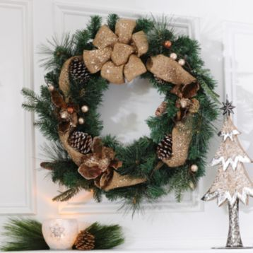 Bring your rustic Christmas decor full circle with our new Burlap Magnolia Wreath! With a classic burlap bow, this wreath sparkles above a warm and cozy fireplace. #Kirkalnds #Home #Wreath #Christmas #HollyJolly