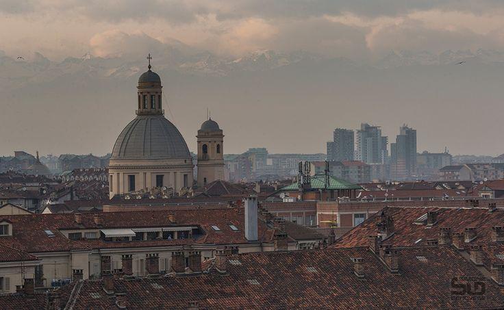Torino - La giornata si chiude con una vista della città di Torino con le ultime luci che illuminano delicatamente le Alpi nascoste dietro un velo di nuvole