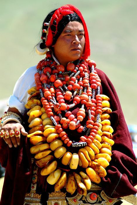 "Tibetean woman with ""statment necklace"". I pretty sure the yellow beads are amber which is very light but still, think this must be quite a load. She's blinging it ""Tibetean-style""."