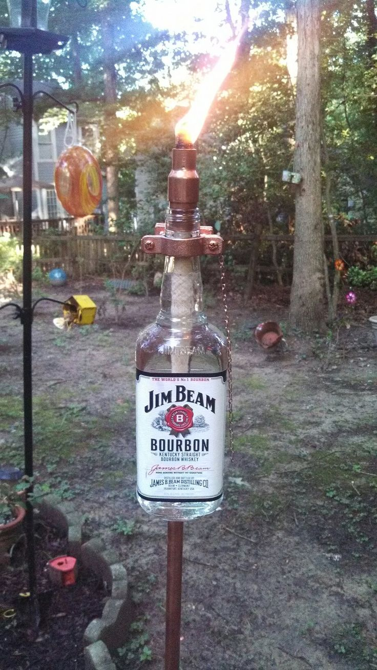 My husband just came up with this Outstanding idea for tiki torches! Liquor  bottles with