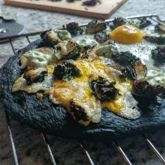 Veggie pizza: pizzabodem van zwarte bonen, belegd met spruitjes en ei