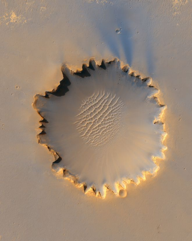 This stunning view of the half-mile-wide Victoria Crater was taken Oct. 3, 2006. The Mars rover Opportunity, which arrived at Victoria five days before this image was taken, is perched at the crater's edge (below). Opportunity explored Victoria crater until August 2008