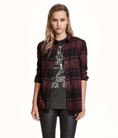 Long-sleeved shirt in plaid cotton flannel with heavily distressed details, turn-down collar, and chest pockets with button.