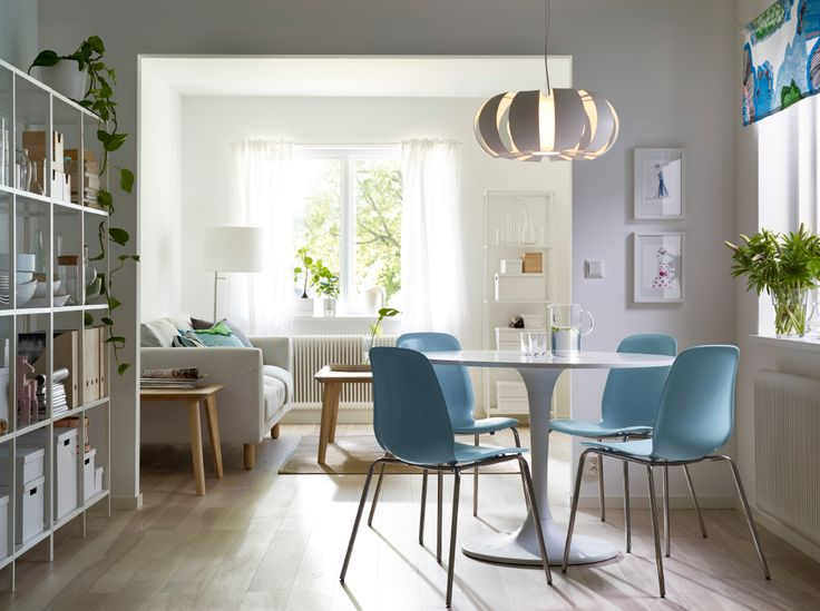 a dining room with a round white dining table combined with light blue chairs with stainless. Black Bedroom Furniture Sets. Home Design Ideas