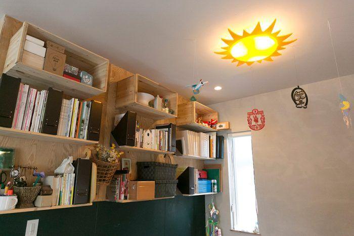 壁の本棚は、なんと麻梨子さんのDIYだそう。リンゴ箱とIKEAで買った棚板がリズミカルに連続する。