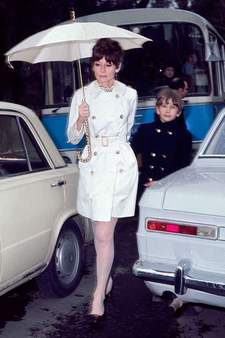 Audrey Hepburn Dotti photographed with her son Sean in Rome (Italy), in February 1969. Audrey was wearing: Trench coat: Burberry (of twill cotton, of the collection for the Autumn/Winter 1966/67). Scarf: Valentino (of his collection for the Autumn/Winter 1968/69). Umbrella: Givenchy Boutique Paris (of the collection for the Spring/Summer of 1967). Shoes: Roger Vivier.