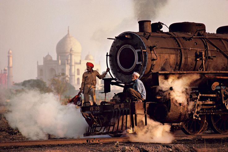 Travelers | Steve McCurry    Agra, Uttar Pradesh, India     From another set called Travellers. Nice contrast between industrial equipment and more modern establishments - good sense of vast space, contrast in class, position.