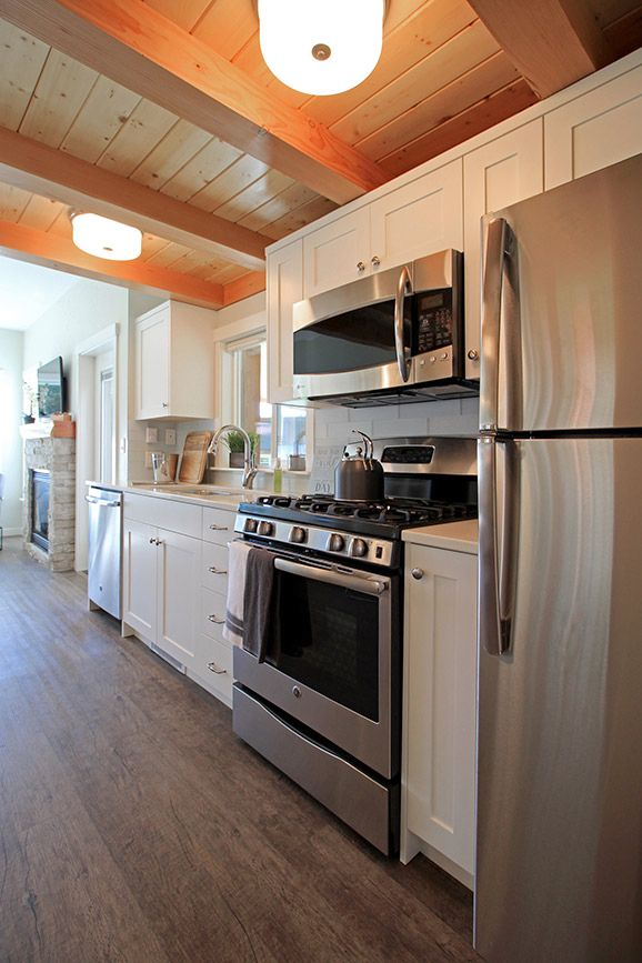 The one-wall kitchen includes a full size dishwasher, freestanding range, and an apartment size refrigerator.
