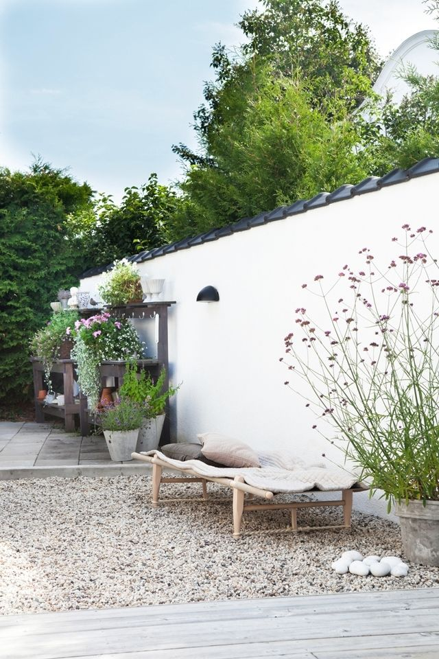 White wall, pot planting, pebbles, cosy cushion, scandinavian