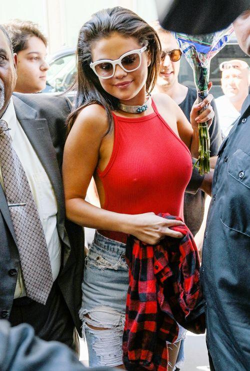 Selena Gomez wears a red Jessa bodysuit from Reformation with Levi's ripped denim.