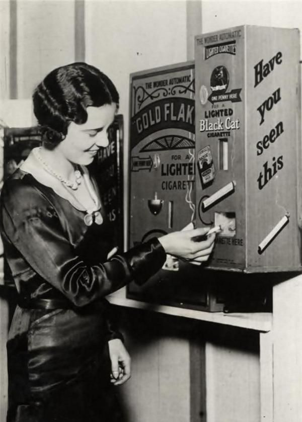 A vending machine that sold already lit cigarettes for a penny. England - 1931