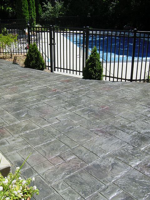 Stamped concrete patio in ashlar slate pattern with bluestone color and red highlights.