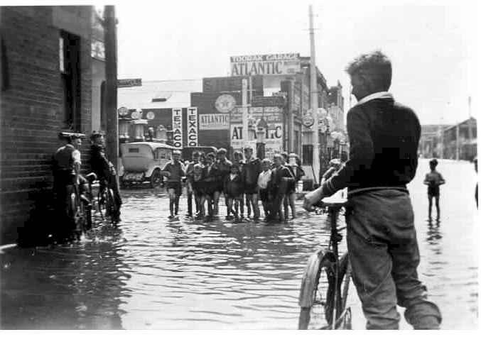 PH 7006. Children wading across Toorak Road, corner Surrey Road, during the 1934 flood.