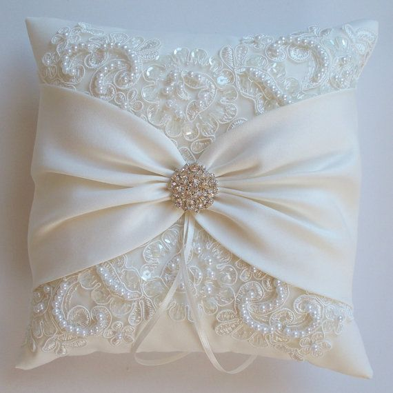The MIRANDA is an ivory matte satin ringbearer pillow decorated with pearled and sequined alencon lace and an ivory satin sash cinched by a crystal