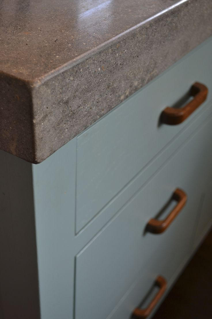 Detail of semi-ground polished concrete worktop Bespoke painted cabinets with vintage wooden handles. www.arnoldskitchens.co.uk