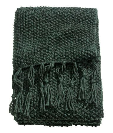 Dark green. Throw in a soft moss knit with wool content. Fringe at short sides.