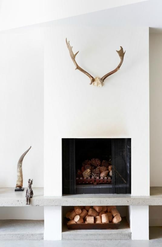 Store wood below. One minimalist sculptural piece above fireplace or minimalist abstract painting.