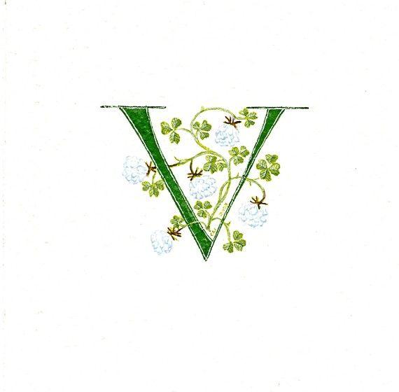 Lettera iniziale v dipinte a mano in verde con fortunato trifoglio bianco su carta ad acquerello, incorniciato allinterno di un monte avorio.