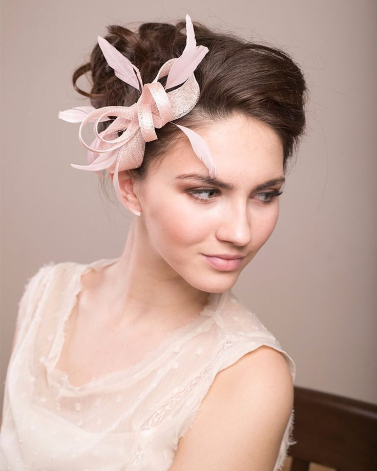 This soft pink ribbon and feather fascinator from BeChicAccessories's Etsy shop is an interesting piece that gives your bridal look that feminine and flirty look you are known for.