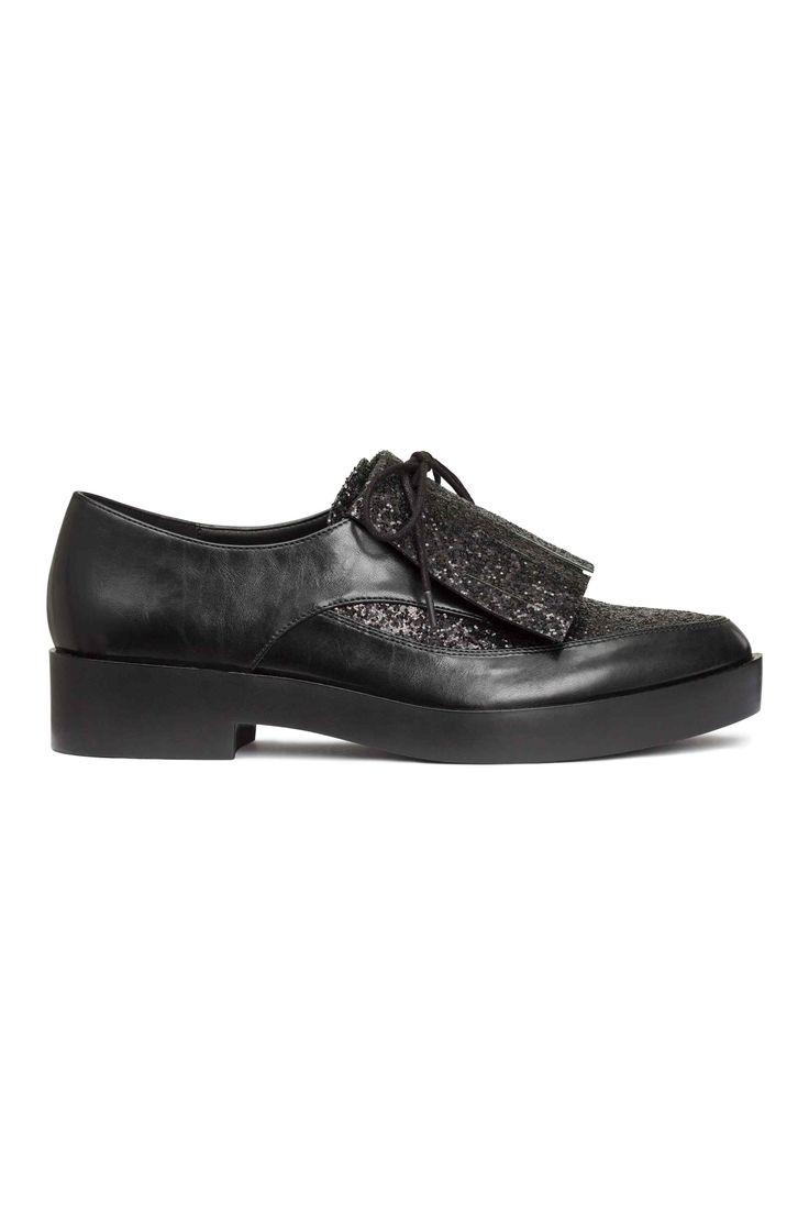 Блестящие туфли: Пара туфель из блестящей искусственной кожи на невысоком каблуке с острым носком. Шнуровка, скрытая бахромой спереди. Платформа спереди 2 см, каблук 3,5 см. Резиновая подошва.