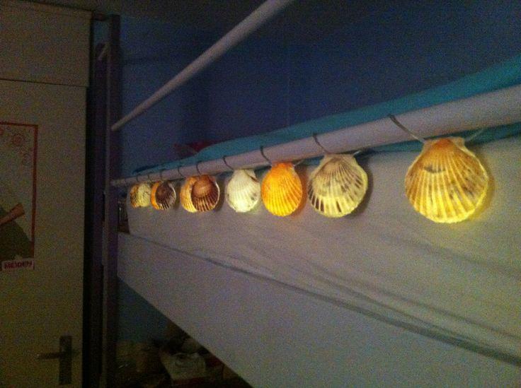 Kerst verlichting met schelpen! Neem twee schelpen die op elkaar passen en lijm er met het lijmpistool 1 lampje in lijm vervolgens de tweede schelp er op! Ga door tot je alle lampjes gehad hebt! Tip gebruik een kort snoer met lampjes...