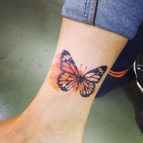 Tatuaje de una mariposa de color naranja situada en el interior...