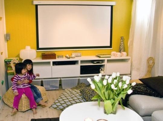 EFTER: Stora kuddar. Ljusa färger i gult, vitt och brunt och bättre belysning gör rummet trivsammare. En ordentlig förvaringsbänk rymmer apparater, filmer och annat. Dubbla gardinskenor med vita gardiner Vivan, Ikea och bakom mörkläggningsgardiner Tupplur, Ikea, är effektivt. På den andra väggen satte inredarna upp klättergrepp, varsam.se, som barnen tycker är roliga. Stora kuddar på golvet och gungstolar i rotting, Ikea PS, Gullholmen.